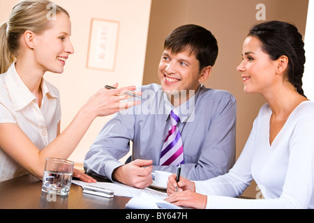 Business people gathered together around the table and discussing working questions - Stock Photo