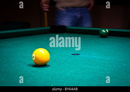 two billiard balls on the table, player on background - Stock Photo