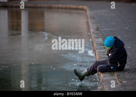 A boy breaks the ice on the frozen pond in Reykjavík, Iceland.  City Hall is reflected in the ice. - Stock Photo