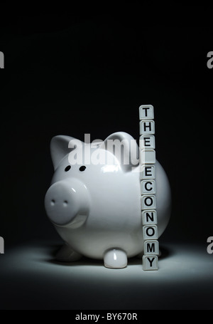 PIGGYBANK WITH WORD TILES SPELLING THE ECONOMY RE ECONOMIC SITUATION BANKS MORTGAGES HOMES FINANCES  SAVINGS HOUSEHOLD - Stock Photo