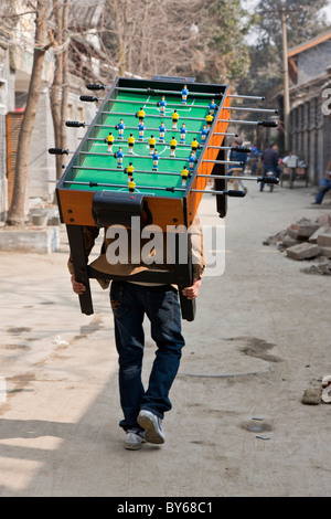 Man carrying Subbuteo football soccer game table on his back through the Hutong, Chengdu, Sichuan Province, China. - Stock Photo