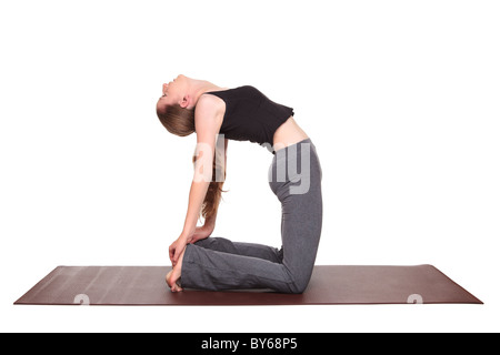 young woman holding the camel pose in yoga stock photo