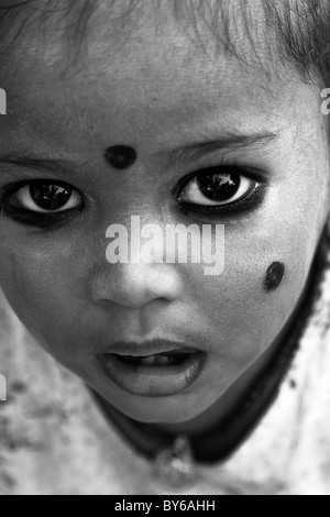 Small Indian child with kohl applied in spots to ward off 'the evil eye', South India. Kohl is an eye cosmetic. - Stock Photo