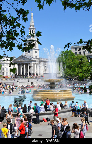 Trafalgar Square fountain London England UK St Martin in the Fields church and spire beyond on a blue sky summer - Stock Photo
