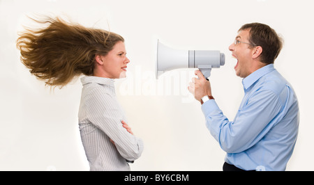 Image of strict boss shouting at businesswoman through loudspeaker so loudly that her hair being blown by strong - Stock Photo