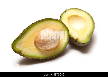 Avocado pear halved and isolated on a white studio background. - Stock Photo