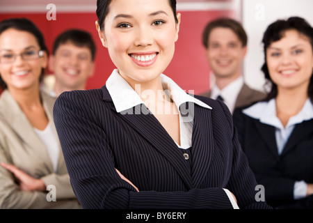 Portrait of cheerful female leader standing in front of her business team - Stock Photo