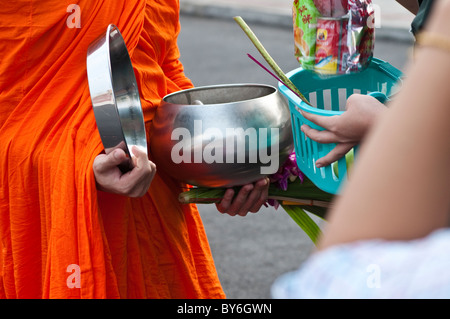 Monks receiving alms from merit-makers in front of Wat Benjamabophit, Bangkok, Thailand - Stock Photo