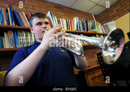 Young male student playing trumpet / cornet in college music room - Stock Photo