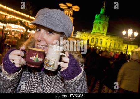 Girl enjoying mulled wine at the Christmas market at Schloss Charlottenburg, Berlin, Germany - Stock Photo