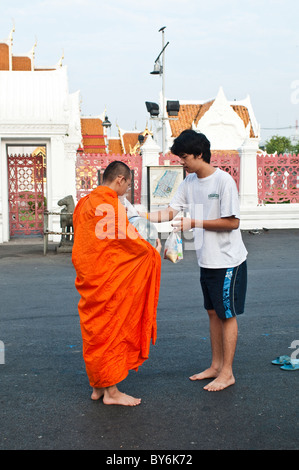 Monk receives alms from a young merit-maker in front of Wat Benjamabophit, Bangkok, Thailand - Stock Photo