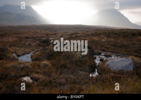 A dramatic view of sunlight breaking through clouds on an Autumnal moorland in the Highlands of Scotland. - Stock Photo
