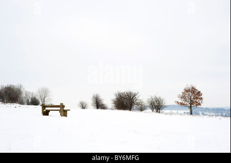 Snow covered bench and view at Rudge Hill near Stroud, Gloucestershire, England, United Kingdom - Stock Photo