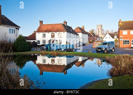 The square, houses, pub and church reflected in the village pond in winter in the village of Aldbourne, Wiltshire, England, UK