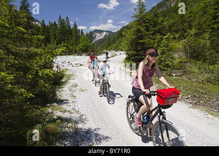 Families cycling along Isar Cycle Route, Hinterau Valley, Karwendel range, Tyrol, Austria - Stock Photo