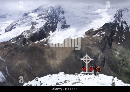 Group of mountaineers standing at a cross on the summit of Vorderer Schmied, valley of Langtauferer Tal, Vinschgau, - Stock Photo