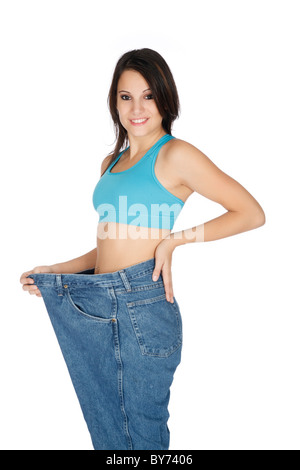 Woman showing weight loss by wearing an old pair of jeans - Stock Photo