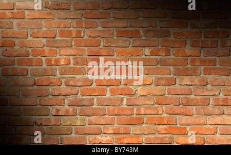 Weathered red brick wall texture lit diagonally - Stock Photo