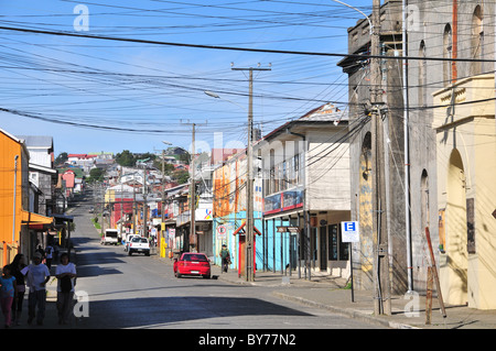 Blue view, from Plaza de Armas, of Banco Estado, shops, pylons and overhead cables, Calle Ramirez, Ancud, Chiloe - Stock Photo