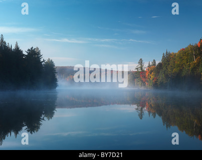 Mist over Smoke lake at dawn. Beautiful fall nature scenery. Algonquin Provincial Park, Ontario, Canada. - Stock Photo