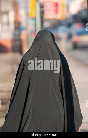 A Muslim woman wearing a Burka walks down Stoney Stanton Rd in Coventry, West Midlands, England - Stock Photo