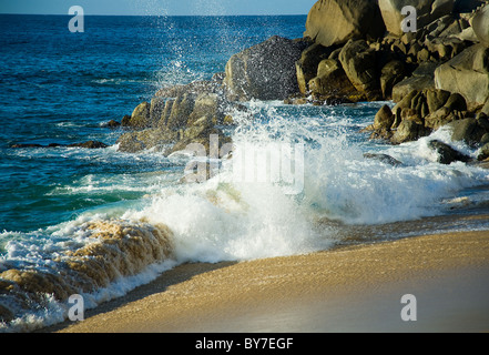 Waves of Pacific ocean near Cabo San Lucas rock rocks water blue salted sand beach - Stock Photo