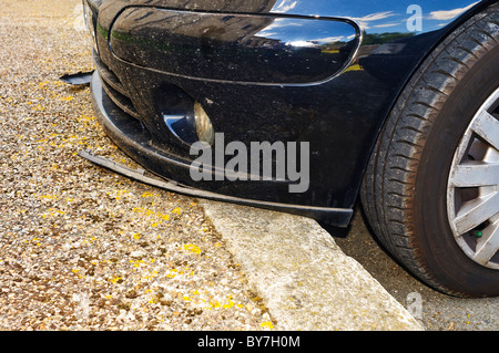 Car over-riding curb damaging front fender – France. - Stock Photo