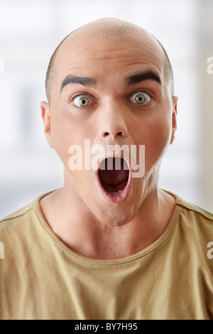 Closeup portrait of a shocked young man looking straight - Stock Photo