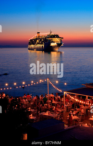 A seaside restaurant and a cruise ship, somewhere between 'Little Venice' and the windmills in the Hora of Mykonos, - Stock Photo