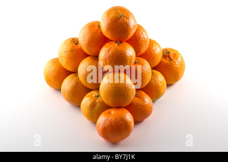 Clementines arranged in a pyramid shape isolated on white background - Stock Photo