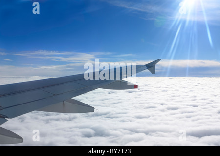 Flying above the clouds with jet aircraft wing and sun flare - Stock Photo