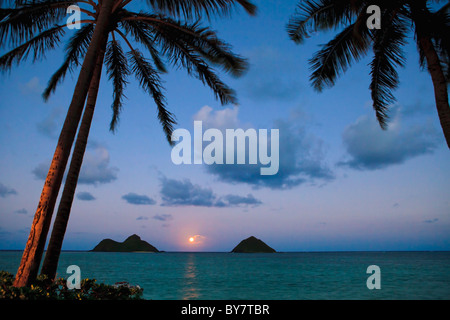 pacific moonrise between the mokulua islands in oahu, hawaii - Stock Photo