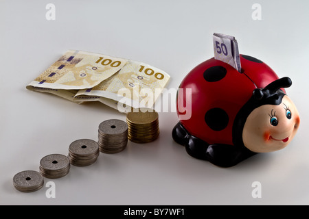 A piggy bank shaped as a ladybird with Danish currency around. isolated on light background - Stock Photo