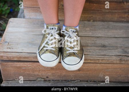 close up of a girl wearing glitter gold converse all star sneakers - Stock Photo