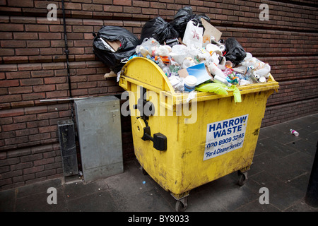 Recycling bins overflowing with rubbish. Designed to recycle waste, these bins are now loaded with trash. - Stock Photo