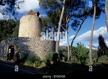 Stone windmill with Sainte-Victoire Mountain in the background, Provence, France. - Stock Photo