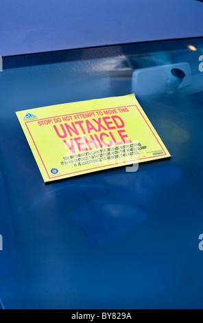 untaxed warning sticker attached to windscreen of vehicle warning not to move clamped vehicle uk - Stock Photo