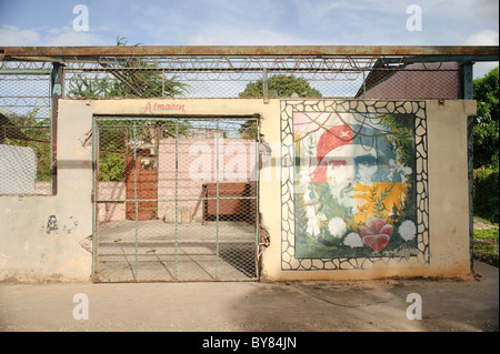 Portrait of Cuban Guerrillero Che Guevara with flowers and colors on a wall of a warehouse in Holguin Cuba - Stock Photo