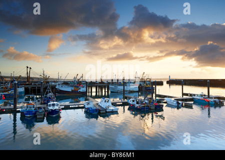 Dramatic rain clouds catching the light of dawn pass over and reflect in the calm waters of Newlyn Harbour - Stock Photo