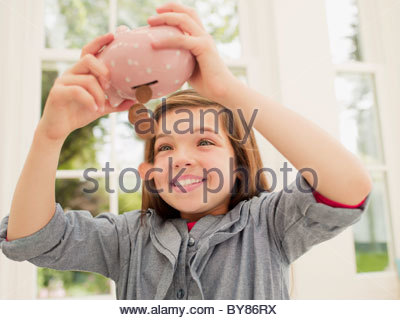 Excited girl emptying coins from piggy bank - Stock Photo