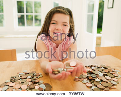 Smiling girl holding handful of coins - Stock Photo