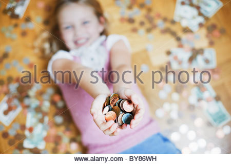 Girl laying on floor holding handful of coins - Stock Photo