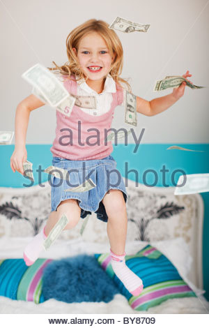 Girl jumping on bed with dollar bills - Stock Photo