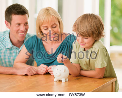 Parents watching son putting coin into piggy bank - Stock Photo