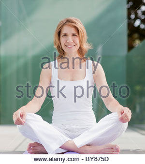 Smiling woman practicing yoga - Stock Photo