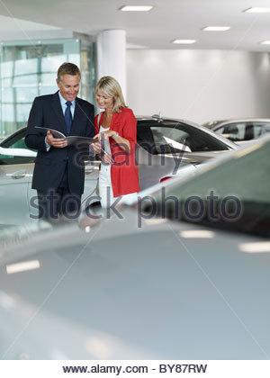 Salesman showing woman brochure in automobile showroom - Stock Photo