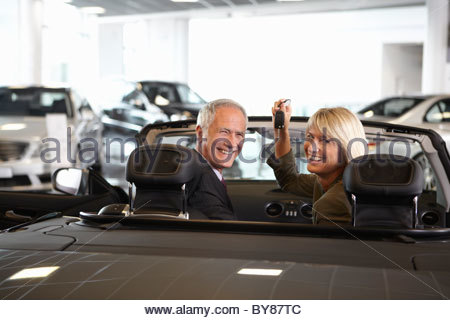 Couple holding keys to new convertible in showroom - Stock Photo