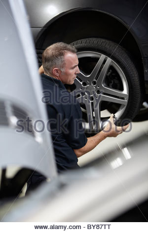 Mechanic replacing tire on car - Stock Photo