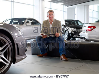 Man looking at brochure in automobile showroom - Stock Photo