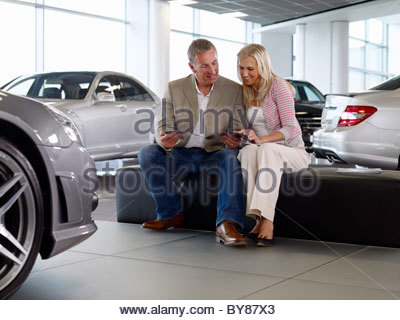 Couple looking at brochure in automobile showroom - Stock Photo